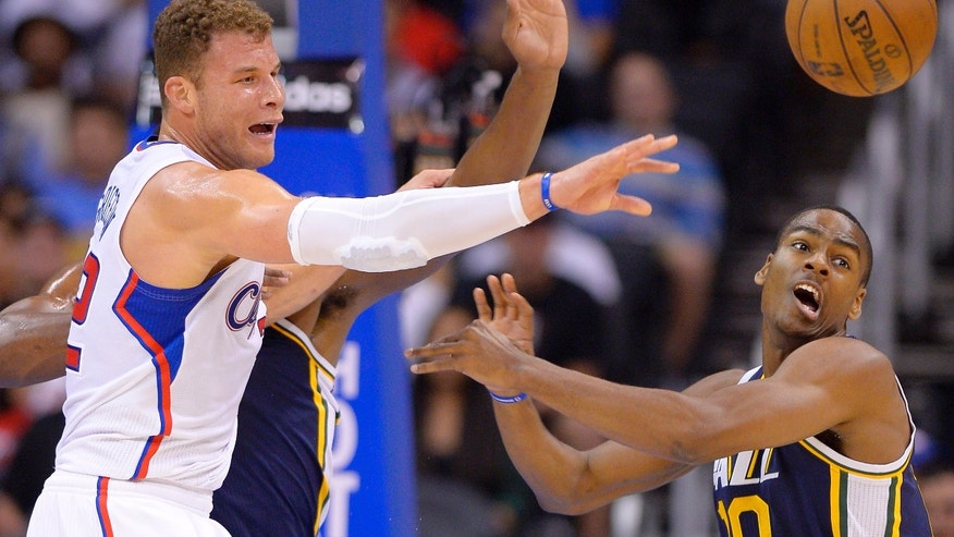 Los Angeles Clippers power forward Blake Griffin, left, passes the ball as Utah Jazz point guard Alec Burks defends during the first half of their NBA basketball game, Wednesday, Oct. 23, 2013, in Los Angeles. (AP Photo/Mark J. Terrill)