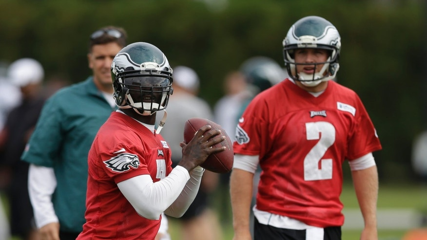 Philadelphia Eagles quarterback Michael Vick, left, throws a pass as quarterback Matt Barkley looks on during practice at the NFL football team's training facility, Tuesday, Oct. 22, 2013, in Philadelphia. (AP Photo/Matt Rourke)