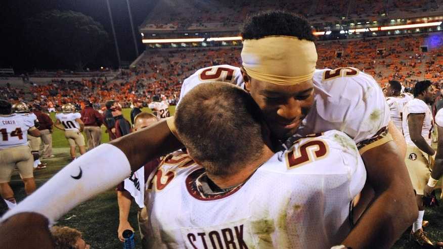 Florida State quarterback Jameis Winston (5) embraces offensive linesman Bryan Stork (52) during the second half of an NCAA college football game, Saturday, Oct. 19, 2013, in Clemson, S.C. Florida State defeated Clemson 51-14. (AP Photo/Mike Stewart)