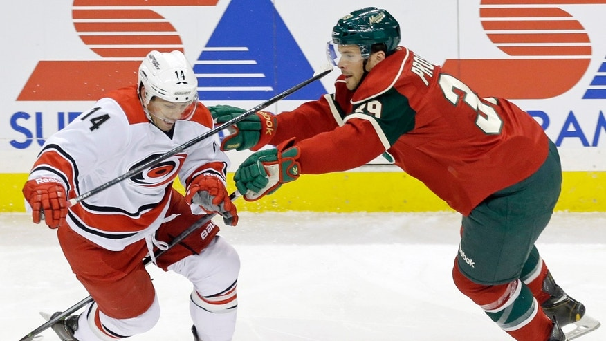 Minnesota Wild's Nate Prosser, right, tries to slow up Carolina Hurricanes' Nathan Gerbe in the first period of an NHL hockey game, Thursday, Oct. 24, 2013, in St. Paul, Minn. (AP Photo/Jim Mone)
