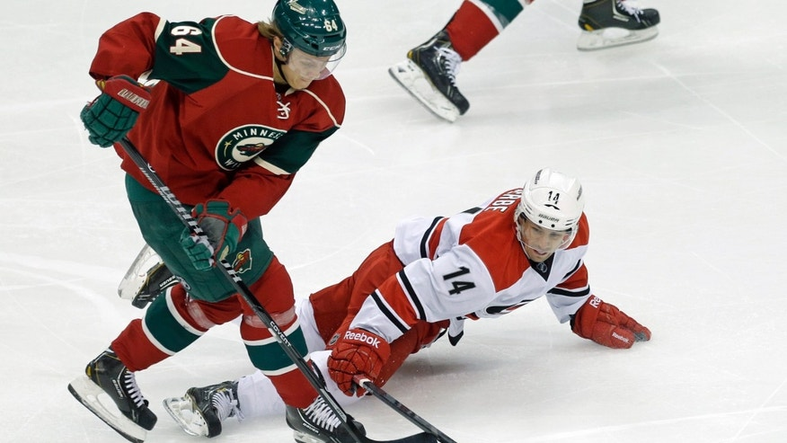 Carolina Hurricanes' Nathan Gerbe, right, tries to reach the puck as Minnesota Wild's Mikael Granlund takes it in the first period of an NHL hockey game Thursday, Oct. 24, 2013, in St. Paul, Minn. (AP Photo/Jim Mone)