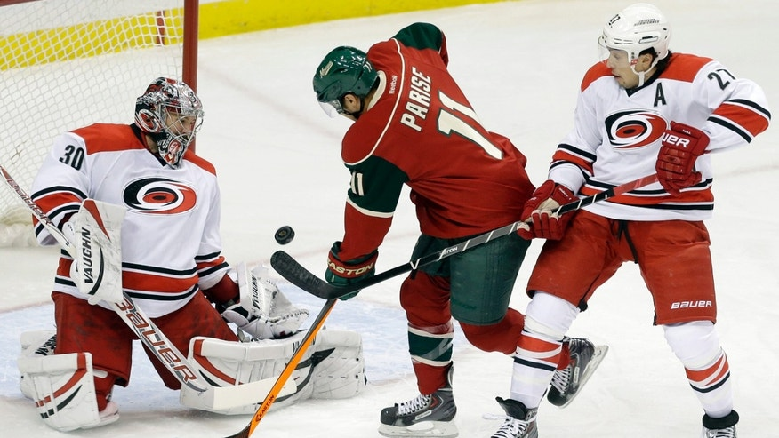 Carolina Hurricanes goalie Cam Ward, left, blocks a shot off the stick of Minnesota Wild's Zach Parise, center, as Hurricanes' Justin Faulk defends in the first period of an NHL hockey game Thursday, Oct. 24, 2013, in St. Paul, Minn. (AP Photo/Jim Mone)