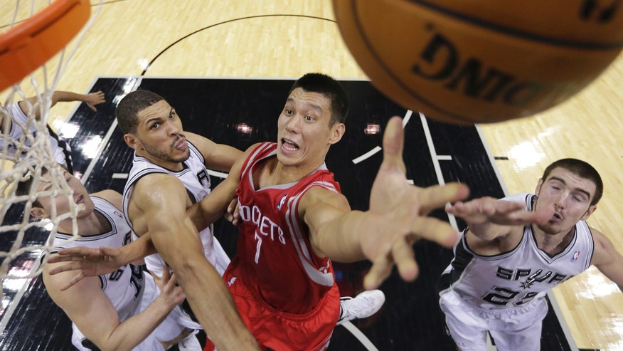 Houston Rockets' Jeremy Lin (7) shoots over San Antonio Spurs' Aron Baynes (16), of Australia, Jeff Ayres, second from left, and Nando De Colo, right, during the first half of a preseason NBA basketball game, Thursday, Oct. 24, 2013, in San Antonio. (AP Photo/Eric Gay)