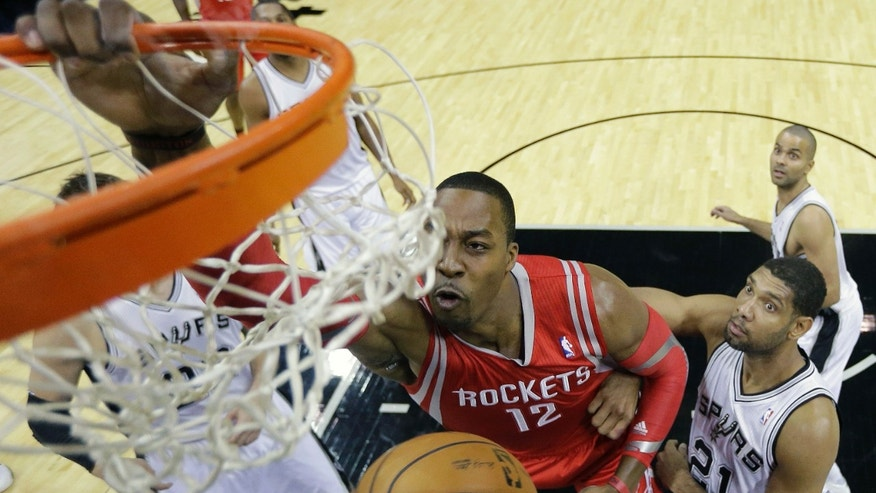 Houston Rockets' Dwight Howard (12) scores over San Antonio Spurs' Tim Duncan (21) during the first half of a preseason NBA basketball game, Thursday, Oct. 24, 2013, in San Antonio. (AP Photo/Eric Gay)