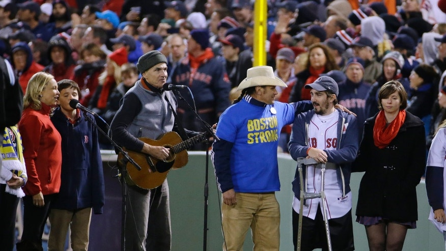 "James Taylor sings ""God Bless America"" alongside Carlos Arredondo, center, and Boston Marathon bombing survivor Jeff Bauman, second from right, during the seventh inning stretch of Game 2 of baseball's World Series between the Boston Red Sox and the St. Louis Cardinals Thursday, Oct. 24, 2013, in Boston. (AP Photo/Matt Slocum)"