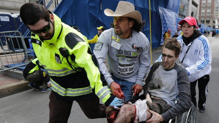 FILE - In this April 15, 2013 file photo, an emergency responder and volunteers, including Carlos Arredondo, center, in the cowboy hat, push Jeff Bauman in a wheel chair after he was injured in an explosion near the finish line of the Boston Marathon, in Boston. Arredondo and Bauman joined James Taylor and other survivors of the Boston Marathon bombing during the seventh inning stretch of Game 2 of baseball's World Series between the Boston Red Sox and the St. Louis Cardinals Thursday, Oct. 24, 2013, in Boston.  (AP Photo/Charles Krupa, File)