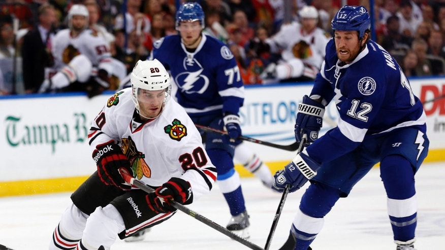 Tampa Bay Lightning left wing Ryan Malone (12) tries to catch Chicago Blackhawks left wing Brandon Saad (20) during the first period of an NHL hockey game on Thursday, Oct. 24, 2013, in Tampa, Fla. (AP Photo/Reinhold Matay)