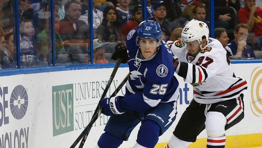 Tampa Bay Lightning defenseman Matt Carle (25) drives past Chicago Blackhawks center Brandon Pirri (37), of Canada, during the first period of an NHL hockey game on Thursday, Oct. 24, 2013, in Tampa, Fla. (AP Photo/Reinhold Matay)