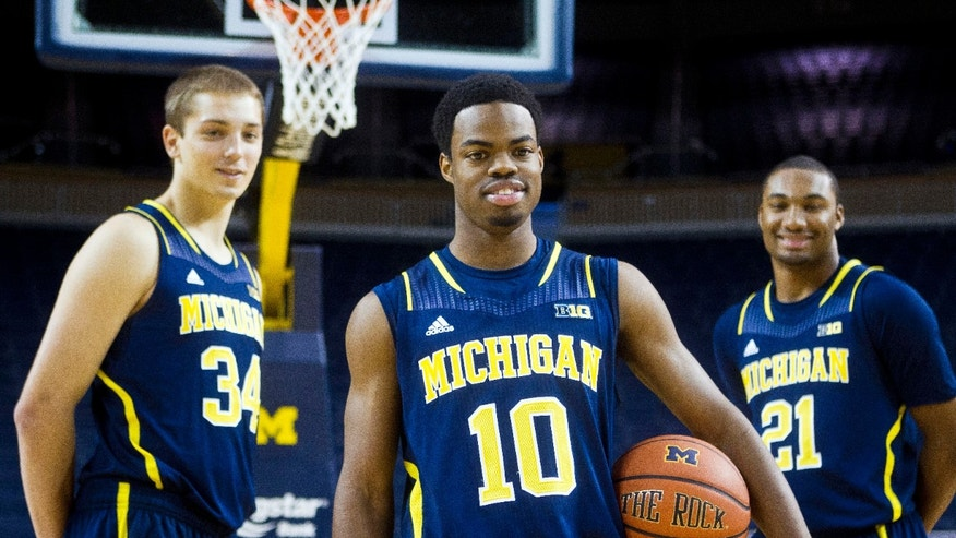 Michigan guard Derrick Walton Jr., center, forward Mark Donnal, left, and guard Zak Irvin pose for portraits during an NCAA college basketball team's preseason media day Thursday, Oct. 24, 2013, at the Crisler Center in Ann Arbor, Mich. (AP Photo/Tony Ding)