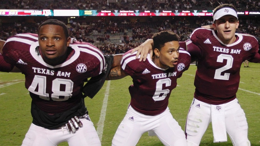 ILE -  In this Sept. 21, 2013, file photo, Texas A&M freshman linebacker Darian Claiborne (48), quarterback Johnny Manziel (2) and defensive back Noel Ellis (6) sing the Aggie War Hymm during an NCAA college football game in College Station, Texas. UCLA and Texas A&M each have played 17 true freshmen this season, tied for most among the programs at the highest level of the game. An Associated Press analysis of depth charts and game reports for the 72 BCS-conference teams and Notre Dame this week showed that 359 freshmen were listed as first- or second-stringers, not including special teams. That represented almost 12 percent of the total of 3,212 players. (AP Photo/Bob Levey)
