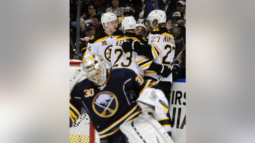 Buffalo Sabres'  Ryan Miller (30) reacts after a goal by Boston Bruins' Dougie Hamilton (27) who celebrates with Carl Soderberg (34), Chris Kelly (23), and Brad Marchand (63) during the second period of an NHL hockey game in Buffalo, N.Y., Wednesday, Oct. 23, 2013. Boston won 5-2.  (AP Photo/Gary Wiepert)