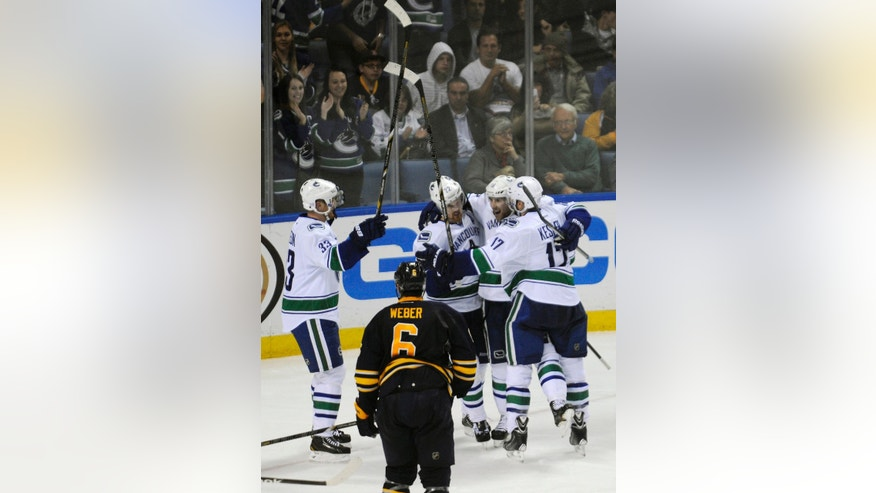 Vancouver Canucks' Henrik Sedin (33), Daniel Sedin (22) , Ryan Stanton (18) and Ryan Kesler (17) celebrate Ryan Stantons' first NHL goal during the third period as Buffalo Sabres' Mike Weber (6) reacts in an NHL hockey game in Buffalo, N.Y., Thursday, Oct. 17, 2013.  Vancouver won 3-0. (AP Photo/Gary Wiepert)