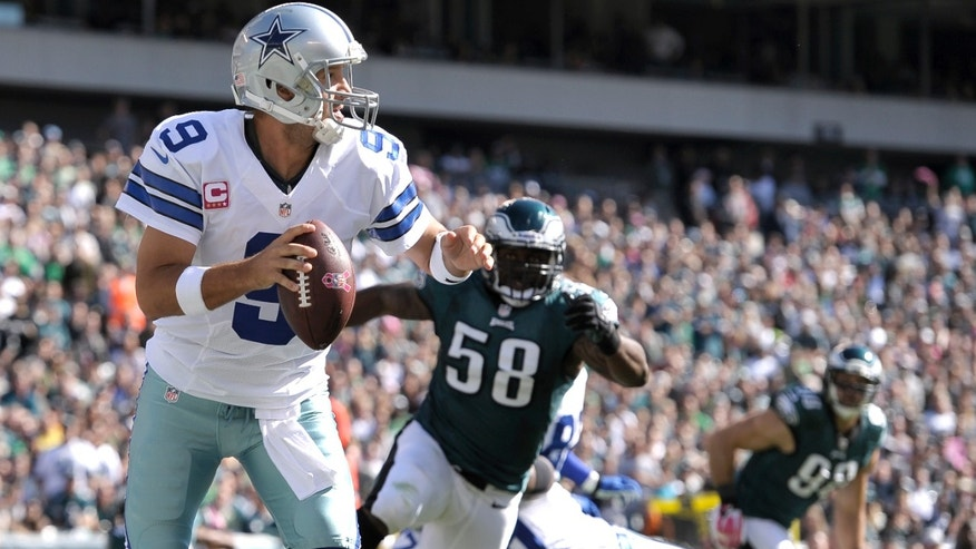 Dallas Cowboys quarterback Tony Romo (9) looks to pass as Philadelphia Eagles outside linebacker Trent Cole (58) chases him during the first half of an NFL football game, Sunday, Oct. 20, 2013, in Philadelphia. (AP Photo/Michael Perez)