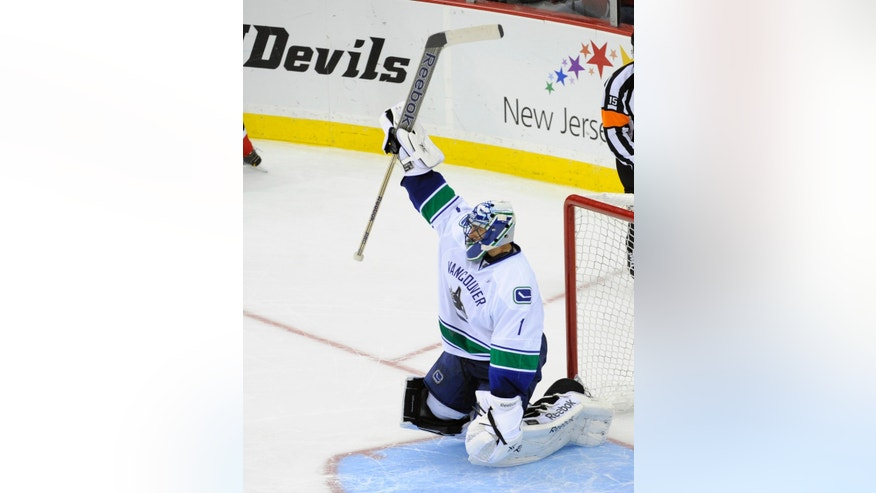 Vancouver Canucks goaltender Roberto Luongo reacts after stopping a shot by New Jersey Devils' Patrik Elias during a shootout in an NHL hockey game on Thursday, Oct. 24, 2013, in Newark, N.J. The Canucks defeated the Devils 3-2. (AP Photo/Bill Kostroun)