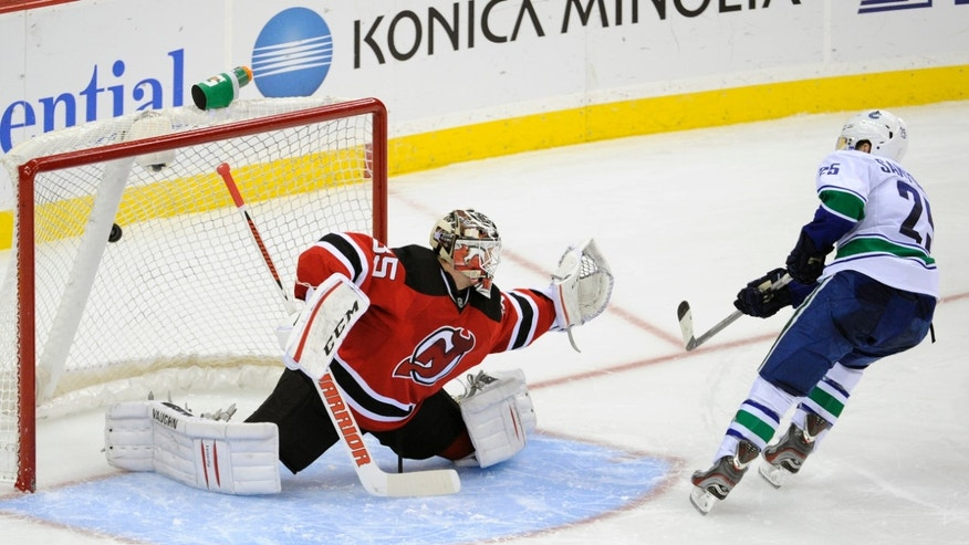 Vancouver Canucks' Mike Santorelli, right, scores a goal against New Jersey Devils goaltender Cory Schneider during an NHL hockey game shootout on Thursday, Oct. 24, 2013, in Newark, N.J. The goal was the only goal in the shootout as the Canucks defeated the Devils 3-2. (AP Photo/Bill Kostroun)