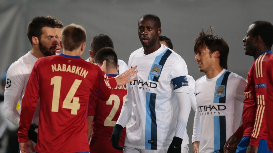 In this photo taken on Wednesday, Oct. 23, 21013, Manchester City's Yaya Toure, center, listens to CSKA's Kirill Nababkin, left, during the Champions League group D soccer match between CSKA Moscow and Manchester City, at Arena Khimki stadium outside Moscow, Russia, on Wednesday, Oct. 23, 2013. Manchester City midfielder Yaya Toure called on UEFA to take action against CSKA Moscow after he was subjected to racist chanting during his team's 2-1 win in the Champions League. The Ivory Coast player said he had told match referee Ovidiu Hategan about the chants during the game in the Russian capital. (AP Photo/Ivan Sekretarev)