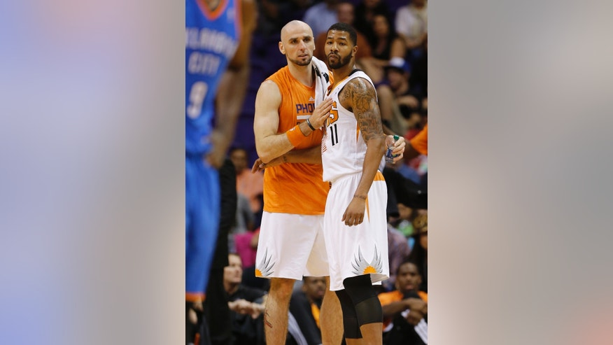 Phoenix Suns' Marcin Gortat, of Poland, slaps Markieff Morris on the chest after Morris was ejected against the Oklahoma Thunder during the second half of an NBA preseason basketball game, Tuesday, Oct. 22, 2013, in Phoenix. (AP Photo/Matt York)