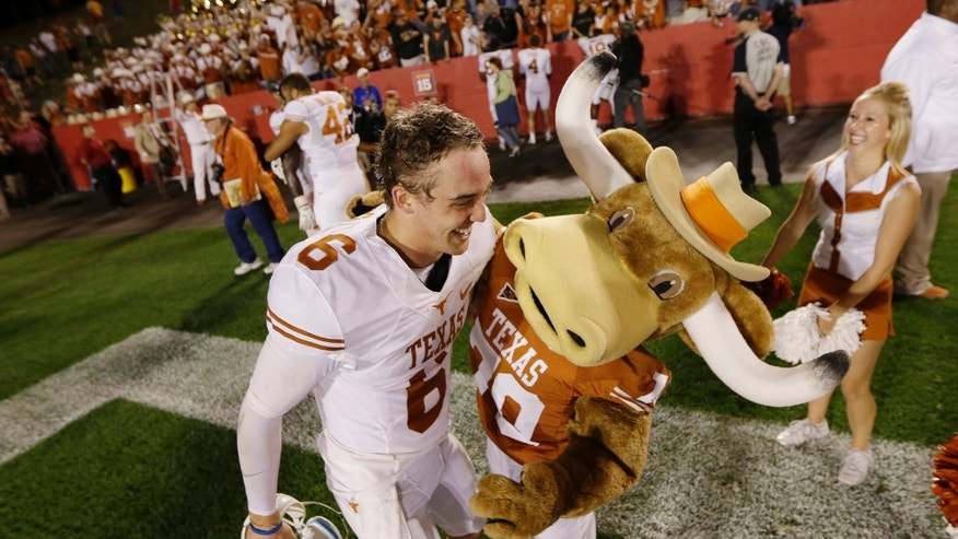 FILE- In this Oct. 3, 2013, file photo, Texas quarterback Case McCoy celebrates with the team mascot after their 31-30 win over Iowa State in an NCAA college football game in Ames, Iowa. McCoy carries himself with the swagger of a national championship-winning quarterback, not a career backup. It's that natural-born confidence that let him step in for injured David Ash and lead the Longhorns to three consecutive victories. (AP Photo/Charlie Neibergall, File)