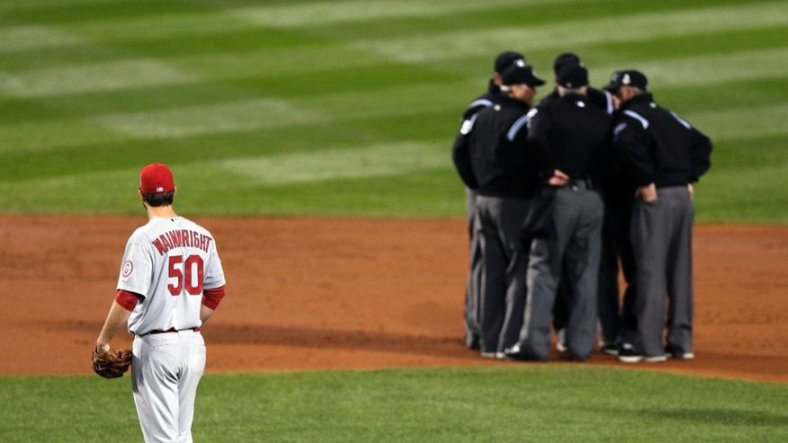 St. Louis Cardinals starting pitcher Adam Wainwright watches as umpires discuss a ruling during the first inning of Game 1 of baseball's World Series against the Boston Red Sox Wednesday, Oct. 23, 2013, in Boston. (AP Photo/Charles Krupa)
