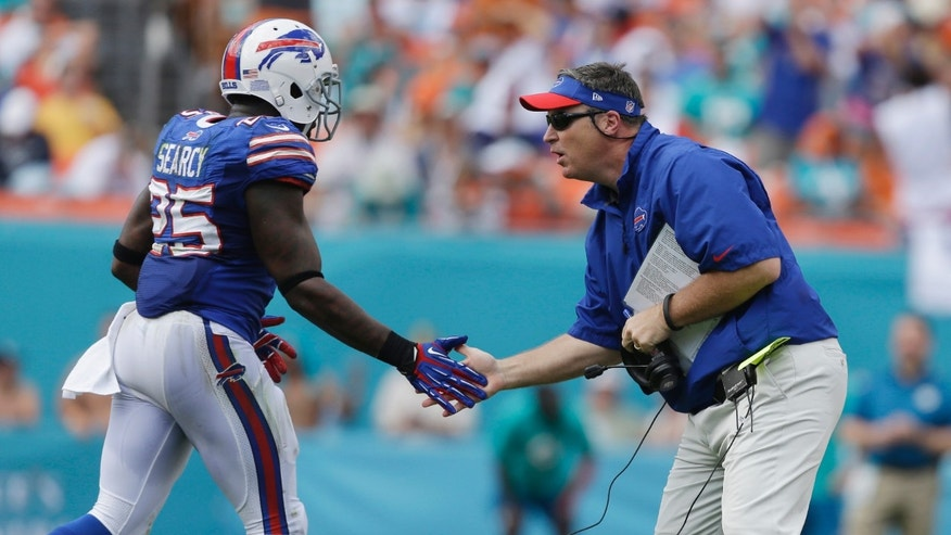 Buffalo Bills head coach Doug Marrone greets Buffalo Bills strong safety Da'Norris Searcy (25) after a play during the first half of an NFL football game against the Miami Dolphins, Sunday, Oct. 20, 2013, in Miami Gardens, Fla. (AP Photo/Lynne Sladky)