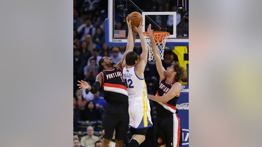 Portland Trail Blazers' LaMarcus Aldridge, left, blocks a shot attempt from Golden State Warriors' Andrew Bogut (12) during the first half of an NBA preseason basketball game on Thursday, Oct. 24, 2013, in Oakland, Calif. (AP Photo/Marcio Jose Sanchez)