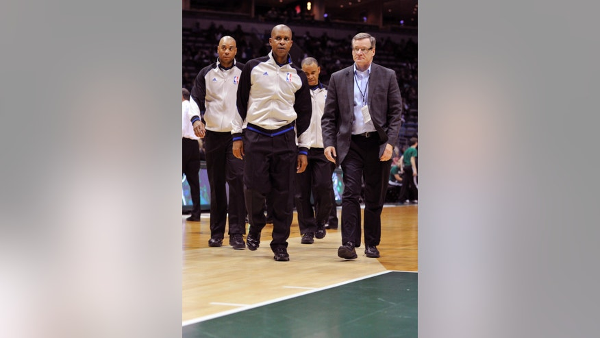 Official's Karl Lane left, Sean Corbin, and Danny Crawford leave the floor after the officials cancelled the game due to an unsafe playing condition with the floor after an NBA preseason basketball game Friday, Oct. 25, 2013, in Milwaukee. The game was canceled in the first quarter after the floor was deemed unsafe to play on. (AP Photo/Jim Prisching)