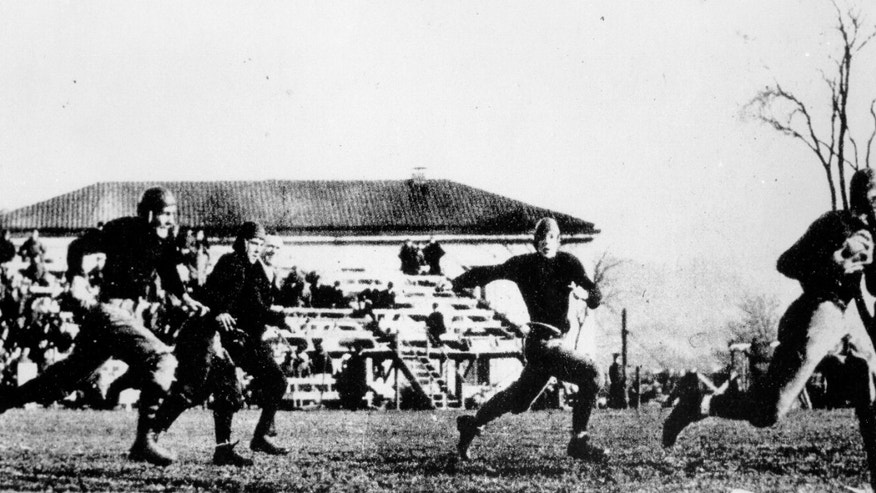 ADVANCE FOR WEEKEND EDITIONS, OCT. 26-27 - This Nov. 1, 1913, photo released by the University of Notre Dame shows Notre Dame football player Knute Rockne, right, making a touchdown against Army after catching a forward pass in West Point, N.Y. The start of World War I was still months away and commercial radio broadcasts were several more years away when the Notre Dame football team boarded a train for West Point 100 years ago for a game against Army that not only brought the Fighting Irish into America's consciousness, but introduced fans to the promise of a fairly newfangled concept known as the forward pass.  (AP Photo/University of Notre Dame)
