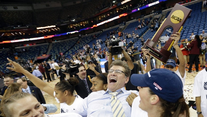 ADVANCE FOR WEEKEND EDITIONS, OCT. 26-27 - FILE - In this April 9, 2013, file photo, Connecticut players celebrate as they carry head coach Geno Auriemma off the court after defeating Louisville 93-60 in the national championship game of the women's Final Four of the NCAA college basketball tournament in New Orleans. With eight players returning from a 35-4 team that won the program's eighth national championship in April, the expectations for this season are greater than ever. (AP Photo/Gerald Herbert, File)