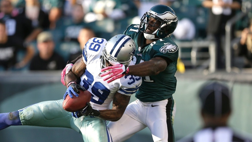 Dallas Cowboys cornerback Brandon Carr, left, intercepts a pass from Philadelphia Eagles quarterback Matt Barkley intended for wide receiver Jason Avant, right, during the second half of an NFL football game, Sunday, Oct. 20, 2013, in Philadelphia. (AP Photo/Matt Rourke)