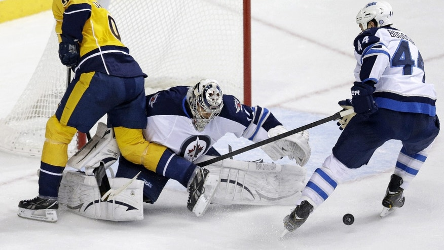 Winnipeg Jets goalie Ondrej Pavelec, of the Czech Republic, blocks a shot by Nashville Predators forward Filip Forsberg (9), of Sweden, as Jets defenseman Zach Bogosian (44) tries to clear the rebound in the second period of an NHL hockey game on Thursday, Oct. 24, 2013, in  Nashville, Tenn. (AP Photo/Mark Humphrey)