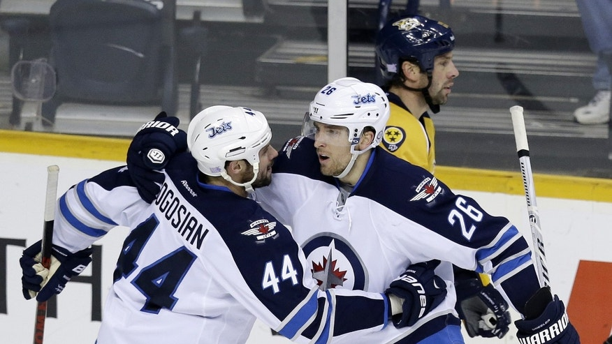 Winnipeg Jets right wing Blake Wheeler (26) celebrates with Zach Bogosian (44) after Wheeler scored against the Nashville Predators in the third period of an NHL hockey game on Thursday, Oct. 24, 2013, in  Nashville, Tenn. Behind them is Predators forward David Legwand.  (AP Photo/Mark Humphrey)