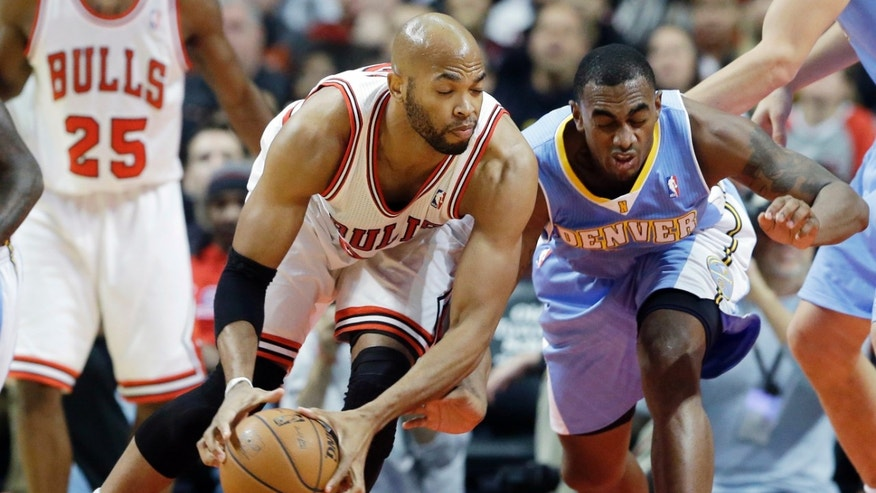 Chicago Bulls forward Taj Gibson, left, battles for a loose ball against Denver Nuggets forward Darrell Arthur during the first half of an NBA preseason basketball game in Chicago on Friday, Oct. 25, 2013. (AP Photo/Nam Y. Huh)