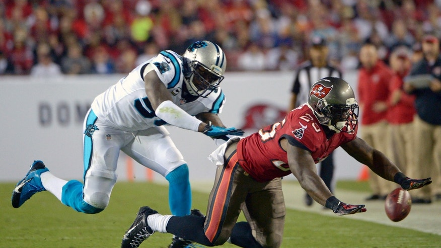 Tampa Bay Buccaneers running back Mike James, right, cannot hang on to a pass as he is guarded by Carolina Panthers outside linebacker Thomas Davis, left, during the first half of an NFL football game in Tampa, Fla., Thursday, Oct. 24, 2013. (AP Photo/Phelan M. Ebenhack)