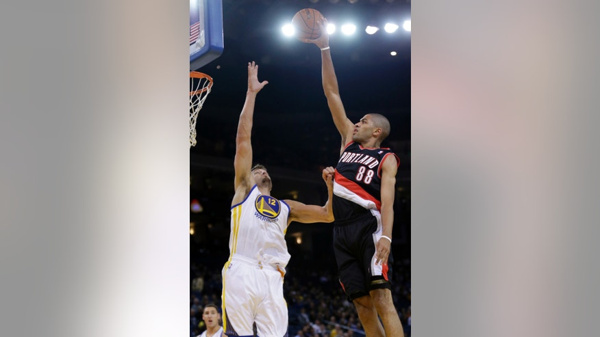 Portland Trail Blazers' Nicolas Batum (88) shoots over Golden State Warriors' Andrew Bogut during the first half of an NBA preseason basketball game on Thursday, Oct. 24, 2013, in Oakland, Calif. (AP Photo/Marcio Jose Sanchez)