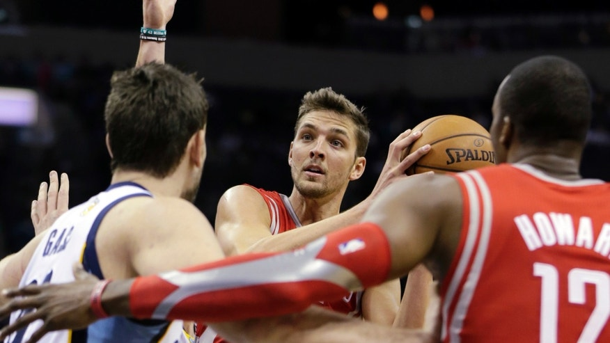 Houston Rockets forward Chandler Parsons, center, shoots over teammate Dwight Howard (12) and Memphis Grizzlies' Marc Gasol, left, of Spain, during the first half of an NBA preseason basketball game in Memphis, Tenn., Friday, Oct. 25, 2013. (AP Photo/Danny Johnston)
