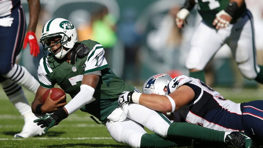 New York Jets quarterback Geno Smith (7) is sacked by New England Patriots' Chris Jones, right, during the first half of an NFL football game Sunday, Oct. 20, 2013, in East Rutherford, N.J.  (AP Photo/Kathy Willens)