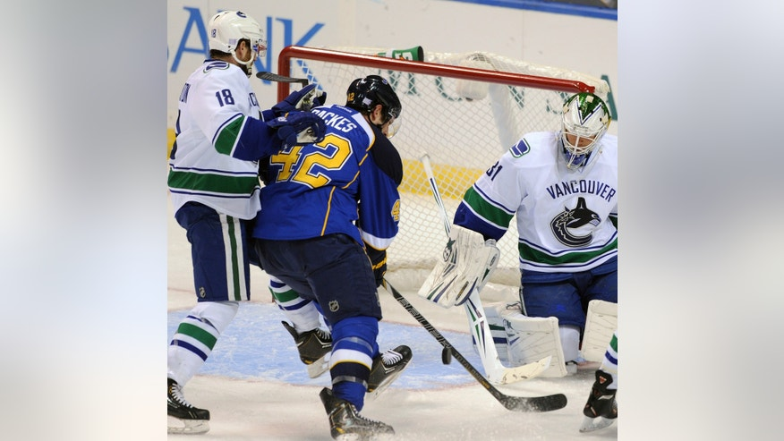 Vancouver Canucks' goalie Eddie Lack (31), of Sweden, blocks a shot by St. Louis Blues' David Backes (42) as Canucks' Ryan Stanton (18) defends during the second period of an NHL hockey game on Friday, Oct. 25, 2013, in St. Louis. (AP Photo/Bill Boyce)