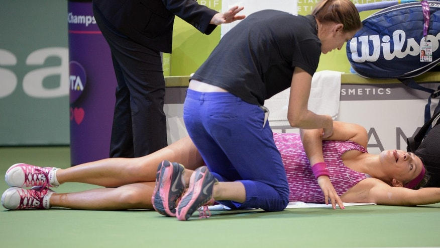 A WTA official speaks with Victoria Azarenka of Belarus, right, after she was injured during her tennis match with Li Na of China at the WTA Championship in Istanbul, Turkey, Friday, Oct. 25, 2013. The world's top female tennis players compete in the championships which runs from Oct. 22 until Oct. 27.(AP Photo)
