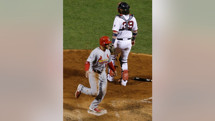 St. Louis Cardinals' Jon Jay crosses home plate in front of Boston Red Sox catcher Jarrod Saltalamacchia after a throwing error during the seventh inning of Game 2 of baseball's World Series Thursday, Oct. 24, 2013, in Boston. (AP Photo/Matt Slocum)