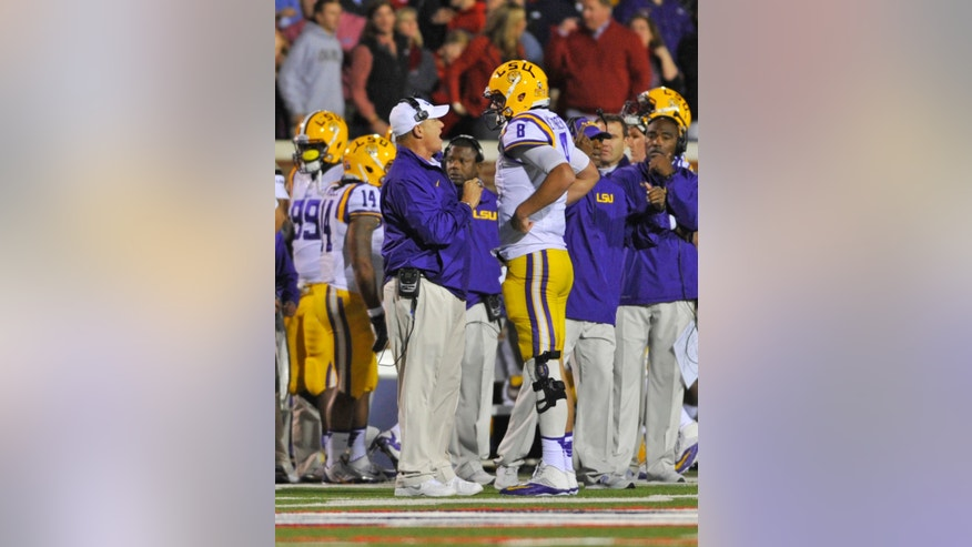 LSU coach Les Miles (left) talks with quarterback Zach Mettenberger (8) following an interception during the first half of an NCAA college football game against Mississippi on Saturday, Oct. 19, 2013, in Oxford, MS. Mississippi won 27-24. (AP Photo/ The Daily Mississippian, Austin McAfee)