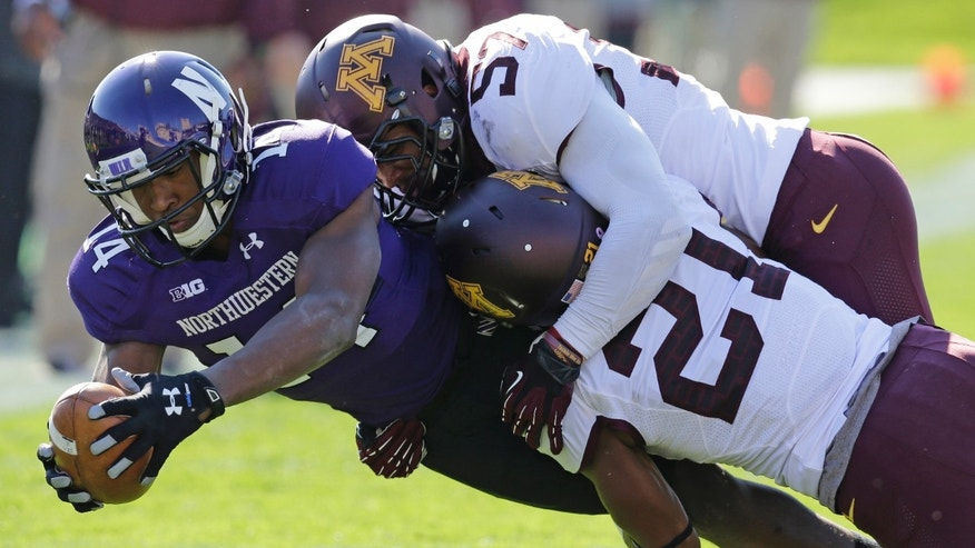 Minnesota defensive back Brock Vereen (21) and linebacker Aaron Hill (57) tackle Northwestern wide receiver Christian Jones (14) during the first half of an NCAA college football game in Evanston, Ill., Saturday, Oct. 19, 2013. (AP Photo/Nam Y. Huh)