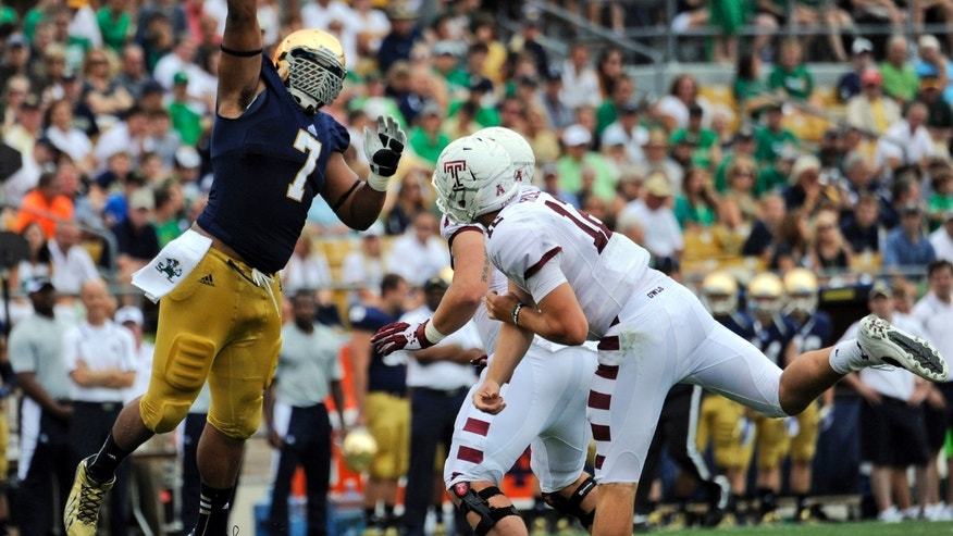 In this Aug. 31, 2013 photo, Notre Dame defensive lineman Stephon Tuitt (7) pressures Temple quarterback Connor Reilly, right, during a college football game in South Bend, Ind. Tuitt feels as comfortable playing the option as getting after quarterbacks, which is why he will be in the center of things against Air Force on Saturday, Oct. 26. (AP Photo/Joe Raymond)