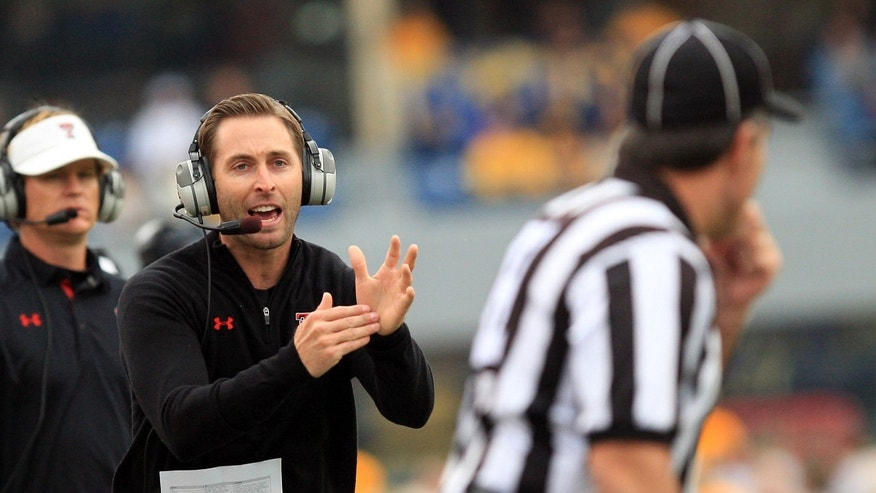 Texas Tech coach Kliff Kingsbury yells for timeout to an official during the second quarter of an NCAA college football game against West Virginia in Morgantown, W.Va., on Saturday, Oct. 19, 2013. Texas Tech won 37-27. (AP Photo/Chris Jackson)