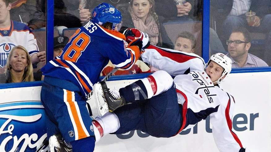 Washington Capitals' Steve Oleksy (61) is checked by Edmonton Oilers' Ryan Jones (28) during the second period of an NHL hockey game, Thursday, Oct. 24, 2013 in Edmonton, Alberta. (AP Photo/The Canadian Press, Jason Franson)