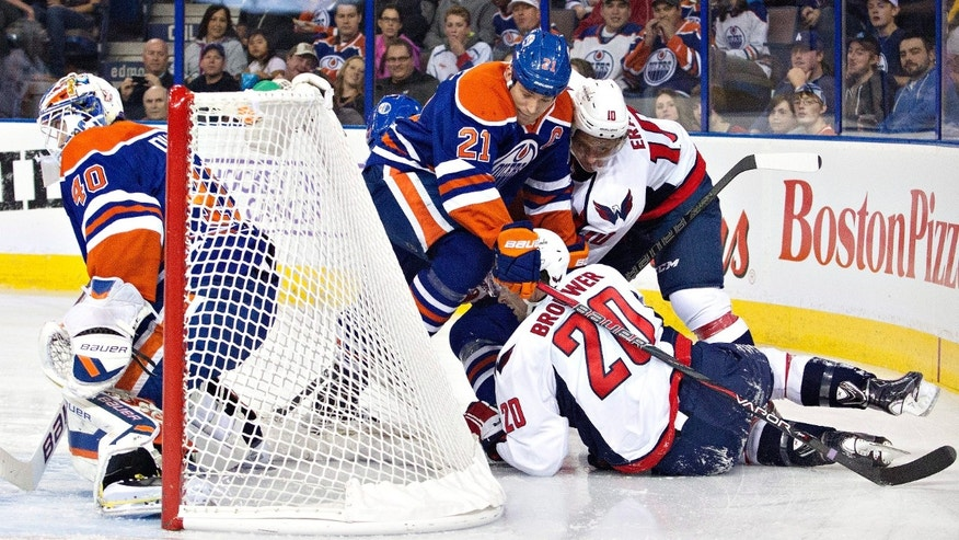 Washington Capitals' Martin Erat (10) and Troy Brouwer (20) battle for the puck with Edmonton Oilers' Andrew Ference (21) as goalie Devan Dubnyk (40) protects the net during the first period of an NHL hockey game, Thursday, Oct. 24, 2013 in Edmonton, Alberta. (AP Photo/The Canadian Press, Jason Franson)