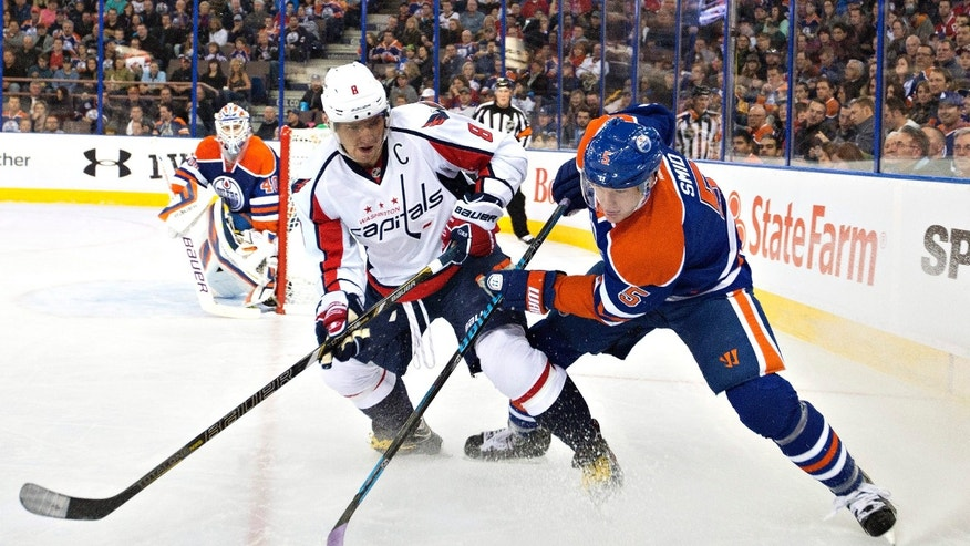 Washington Capitals' Alex Ovechkin (8) and Edmonton Oilers' Ladislav Smid (5) battle for the puck in the corner during the first period of an NHL hockey game, Thursday, Oct. 24, 2013 in Edmonton, Alberta. (AP Photo/The Canadian Press, Jason Franson)