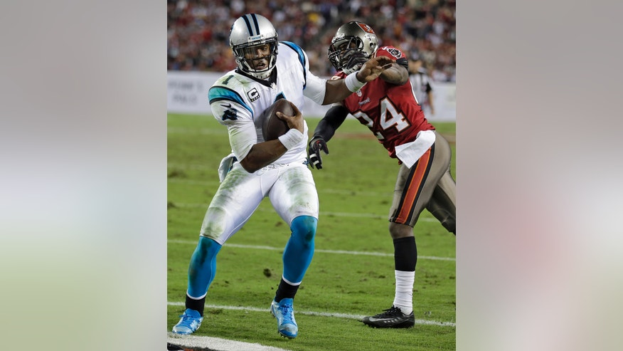 Carolina Panthers quarterback Cam Newton (1) pushes off Tampa Bay Buccaneers cornerback Darrelle Revis (24) to score on a 6-yard touchdown run during the third quarter of an NFL football game on Thursday, Oct. 24, 2013, in Tampa, Fla. (AP Photo/Chris O'Meara)