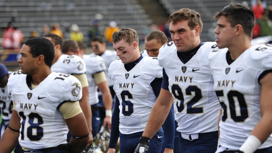 Navy kicker Nick Sloan (6) and his teammate walk off the field after a 45-44 double-overtime loss to Toledo in an NCAA college football game in Toledo, Ohio, Saturday, Oct. 19, 2013. Sloan missed an extra point in double overtime. (AP Photo/David Richard)