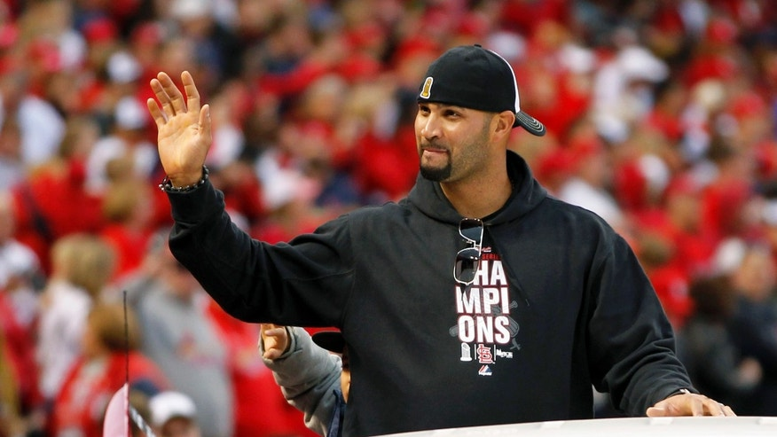 FILE - In this Oct. 30, 2011, file photo, former St. Louis Cardinals player Albert Pujols waves to fans at Busch Stadium during a parade in celebration of the Cardinals' 11th World Series victory in St. Louis. Pujols' exit had no effect on the Cardinals, who have not missed the three-time NL MVP. (AP Photo/Jeff Roberson, File)