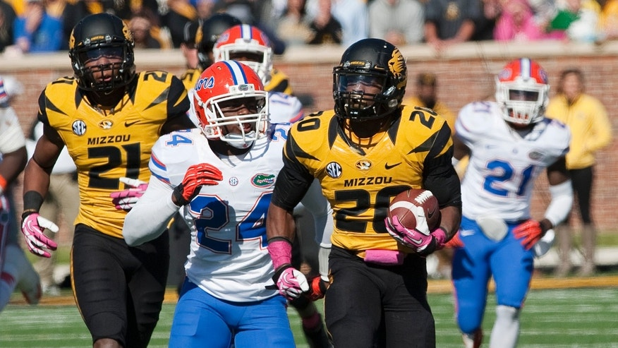 Missouri running back Henry Josey, right runs past Florida's Brian Poole, center, as teammate Bud Sasser, left, runs behind during the fourth quarter of an NCAA college football game Saturday, Oct. 19, 2013, in Columbia, Mo. Josey led all rushers with 137 yards in Missouri's 36-17 victory. (AP Photo/L.G. Patterson)